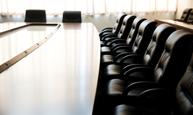 empty boardroom with a row of empty black office chairs and empty table