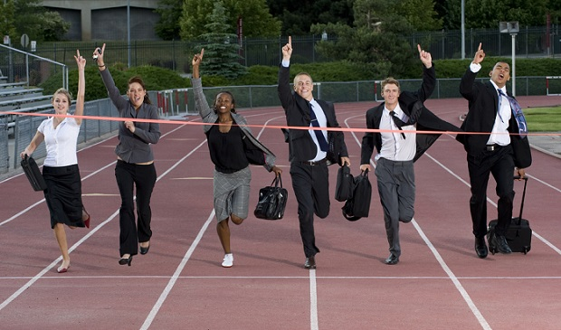 various business people carrying briefcases running together to finish line