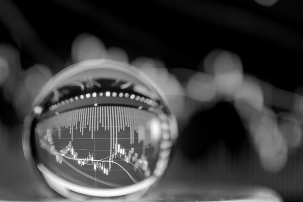 black and white photo of crystal ball with stock or financial chart inside it