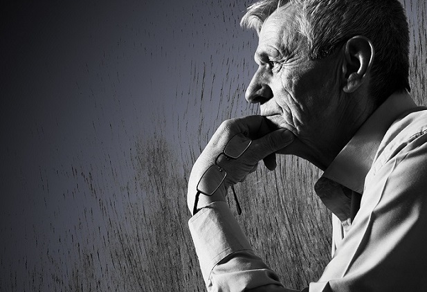Pensive older man with chin on hand