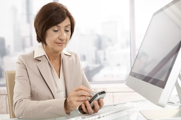 older brunette business woman at computer using cellphone