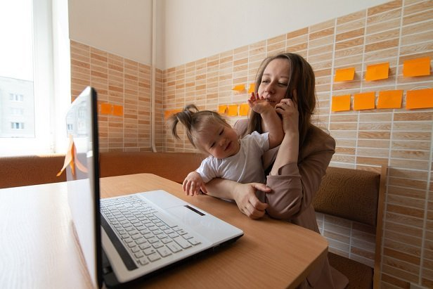 woman at kitchen table on computer while child cries in her lap