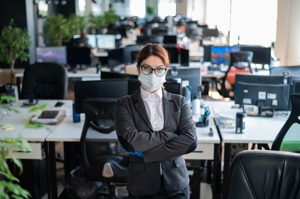 business woman in empty office wearing mask