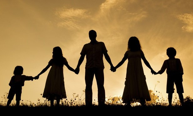 silhouette of five person family holding hands on a hill