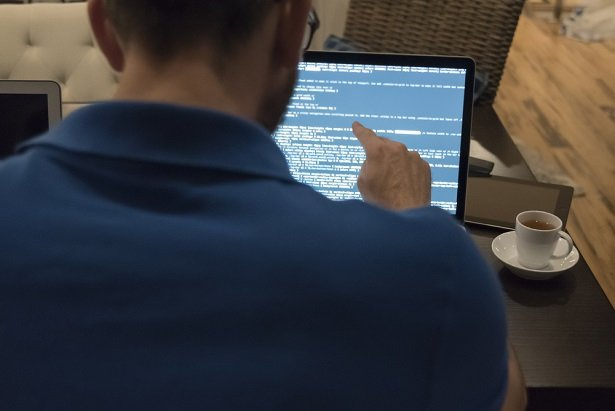 male white IT pro in a blue polo shirt at screen looking at lines of code