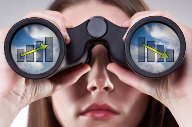 woman looking through binoculars that have bar charts on them
