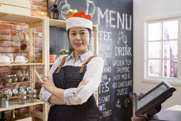 female barista or coffee shop counter woman wearing santa hat