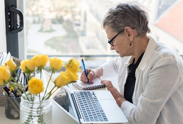 woman at computer by window writing notes