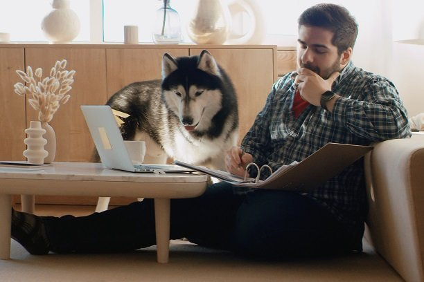 Man sitting beside sofa with laptop and his dog beside him and a notebook on his lap