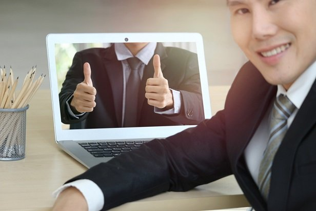 man at laptop with colleague online giving a thumbs up