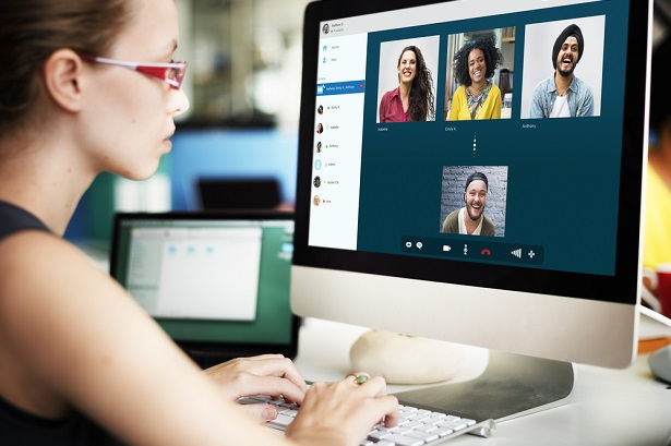 woman at computer screen working remotely with four colleagues via a virtual meeting