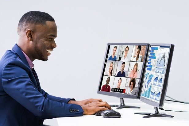 smiling man at computer having a virtual meeting while looking at financial charts
