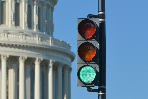 closeup of dome of US capitol building with a green traffic light in front of it