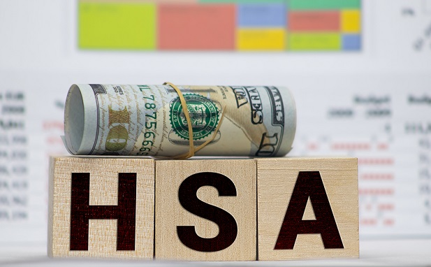 3 letter blocks spelling HSA on top of which rests a roll of rubberbanded currency