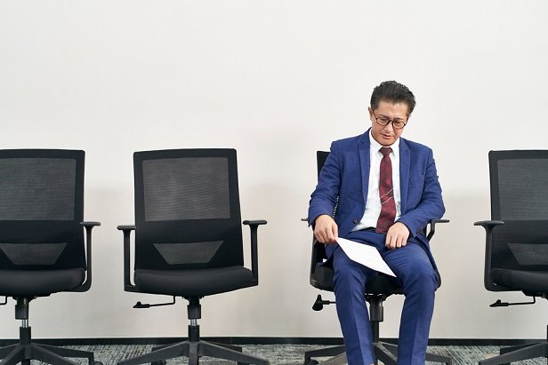 man in business suit sitting in waiting room