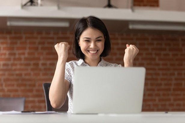 woman at laptop with fists raised in triumph