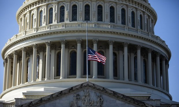 closeup of U.S. Capitol building with flag at half mast