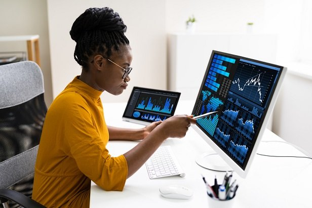 woman looking at monitor as she goes over her investments