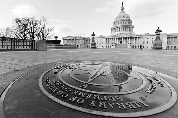 black and white photo of the U.S. Capitol building and compass seal