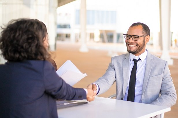 man and woman in business suits shaking hands
