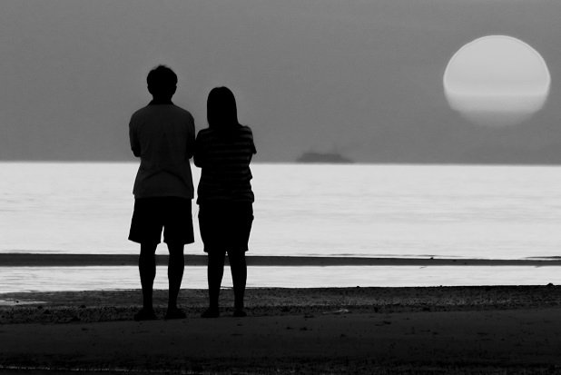 man and woman silhouetted as they stand by a lake watching rising moon