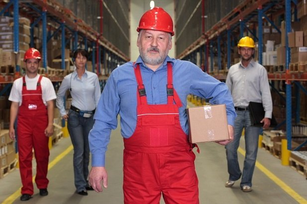 older worker in hardhat in warehouse job with coworkers standing behind him