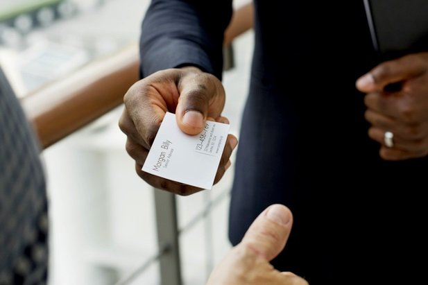 closeup of business man handing card to person