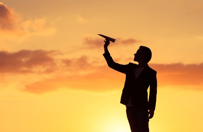 man silhouetted against sunset holding paper airplane