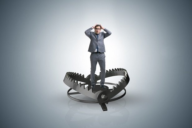 man standing in giant bear claw trap
