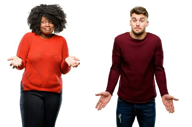 woman and man holding arms out to express confusion