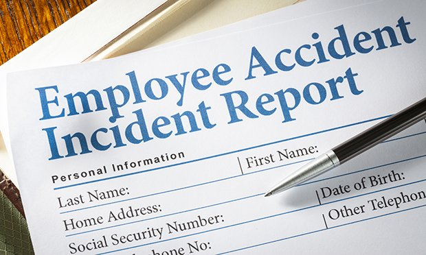 Employee Accident Report Claim Form on desk with pen