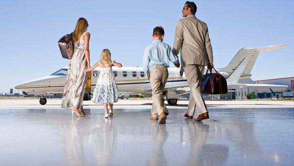 A wealthy family walks toward its jet