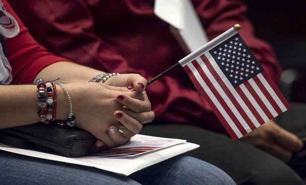An applicant for U.S. citizenship holds an American flag during a naturalization ceremony at the Evo A. DeConcini U.S. Courthouse in Tucson, Arizona, U.S., on Friday, Sept. 16, 2016. From October 2015 through June 2016, 718,000 legal permanent residents applied for citizenship, up 8 percent compared to the same period leading up to the 2012 presidential election, according to federal data. Photographer: David Paul Morris/Bloomberg