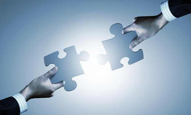 Business hands holding puzzle pieces