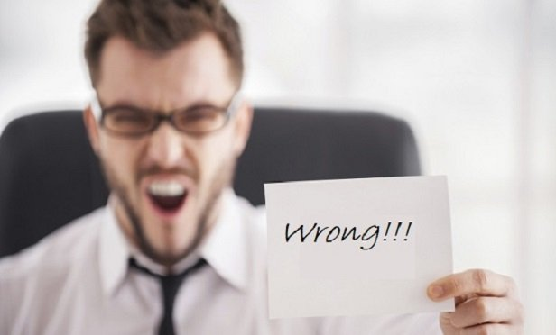 """Man with a note saying, """"Wrong!"""""""