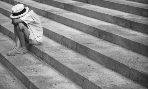 Girl sitting on steps with face down, outdoors (B&W)