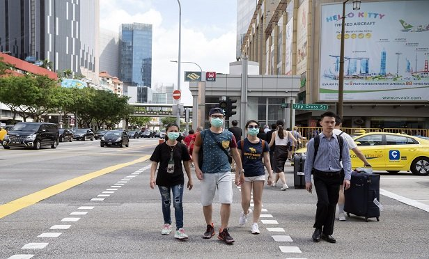 Pedestrians wearing face masks, crossing a road