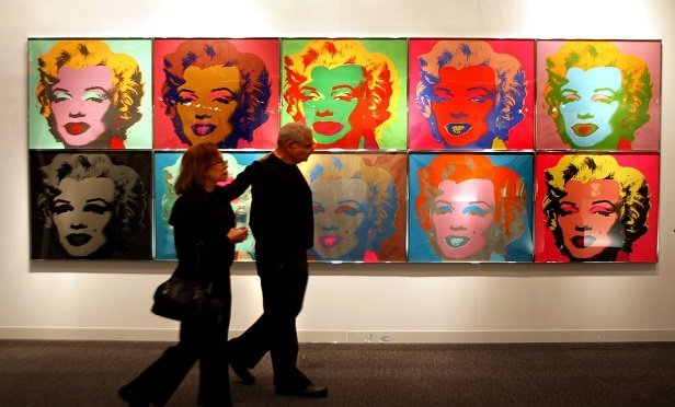 """Jill and Allen Greenwald stroll past Andy Warhol's """"Marilyn Monroe 1967"""" at the Art Basel contemporary art show in Miami Beach, Florida, on Thursday, December 4, 2003. The exhibit, a showcase of works by more than 1,000 artists, is the """"sister event"""" to the influential Art Basel show in Switzerland. Photographer: Mike Fuentes/Bloomberg News"""