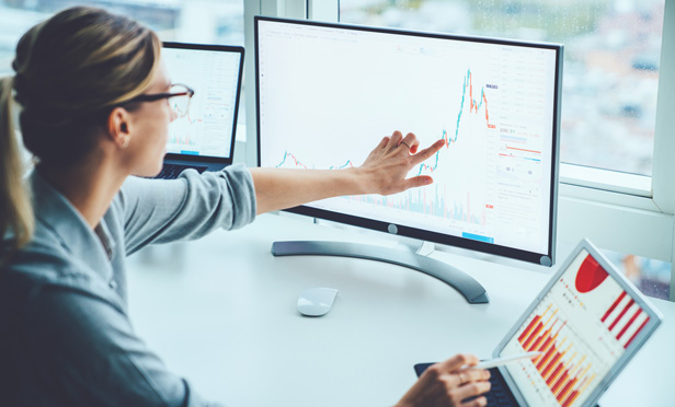 Businesswoman pointing at stock chart on screen