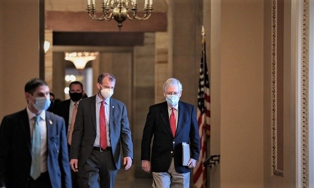 Senate Majority Leader Mitch McConnell, a Republican from Kentucky, right, wears a protective mask while walking to the Senate floor at the U.S. Capitol in Washington Dec. 11, 2020. (Credit: Cheriss May/Bloomberg)